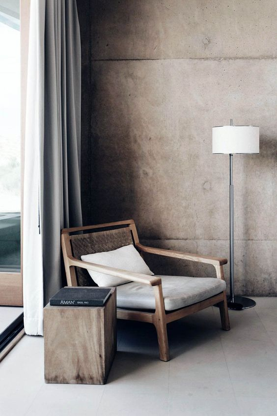 corner seat with woven back and wood frame log side table modern floor lamp with white lampshade bare concrete walls