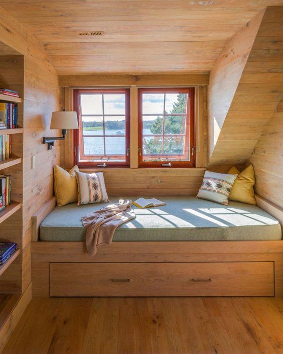 cozy reading nook fully covered in wood a couple of glass windows with red frame and trims bench seat with cushion addition and under drawer some throw pillows