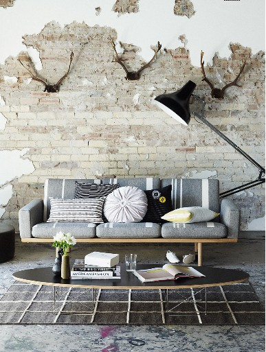 crisp white walls with worn out & exposed brick accents modern furniture set modern industrial floor lamp modern area rug in black concrete floors