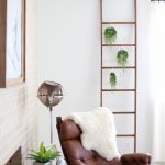 Decorative Leaning Ladder Made Of Wood Some Hanging Houseplants On Pots Tufted Leather Armchair Round Top Wood Side Table