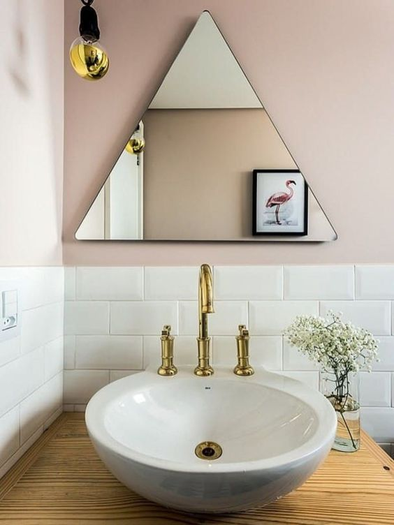 frameless triangle wall mirror white sink with brass faucet wood countertop white ceramic subway tile backsplash ultra light pink walls