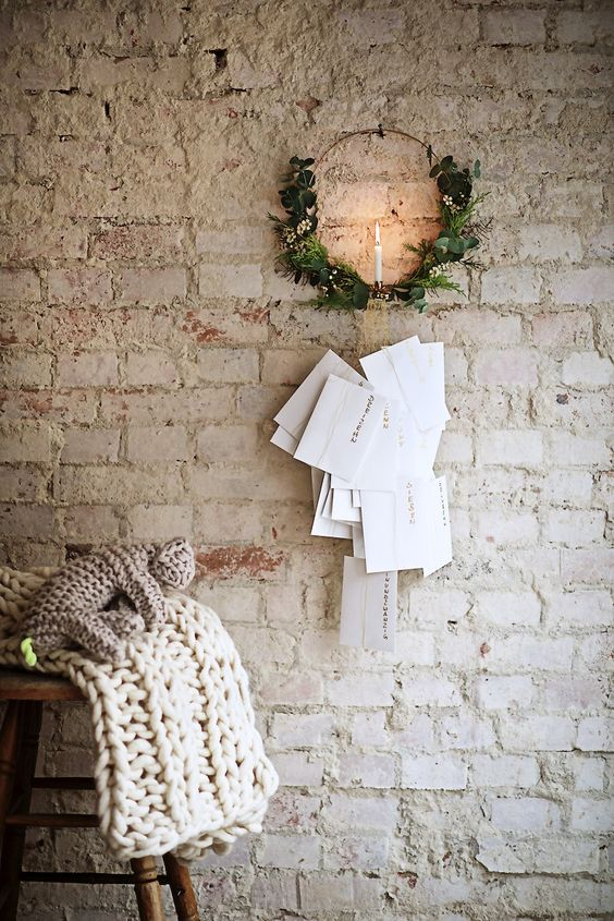 greenery wreath with candle holder in center whitewashed brick walls