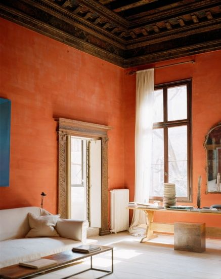 high ceilings with carving details bold orange stucco walls light tone floors large size window with floor to ceiling curtains white sofa modern coffee table