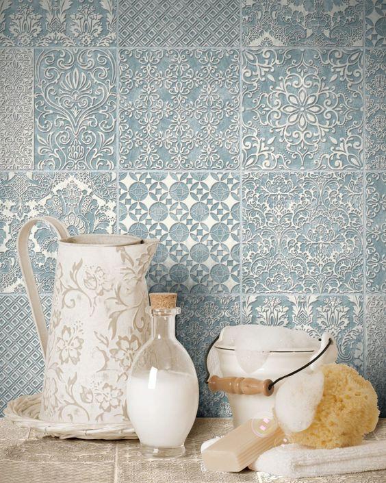light blue tile backsplash with embossed floral and geometric motifs