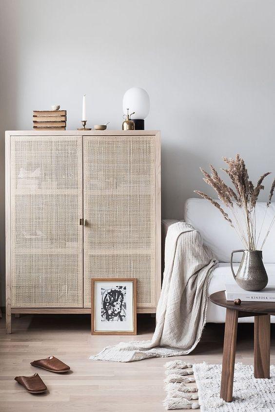 light wood dresser in rustic minimalist style white sofa with throw blanket wood coffee table wool area rug light wood floors