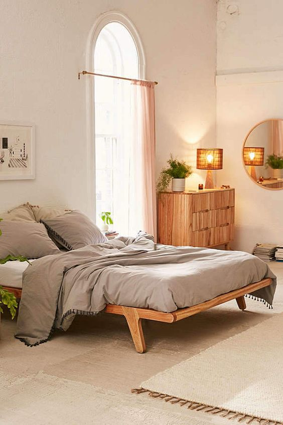 light wood platform bed frame with slanted legs and slatted surface gray duvet cover and shams wood dresser