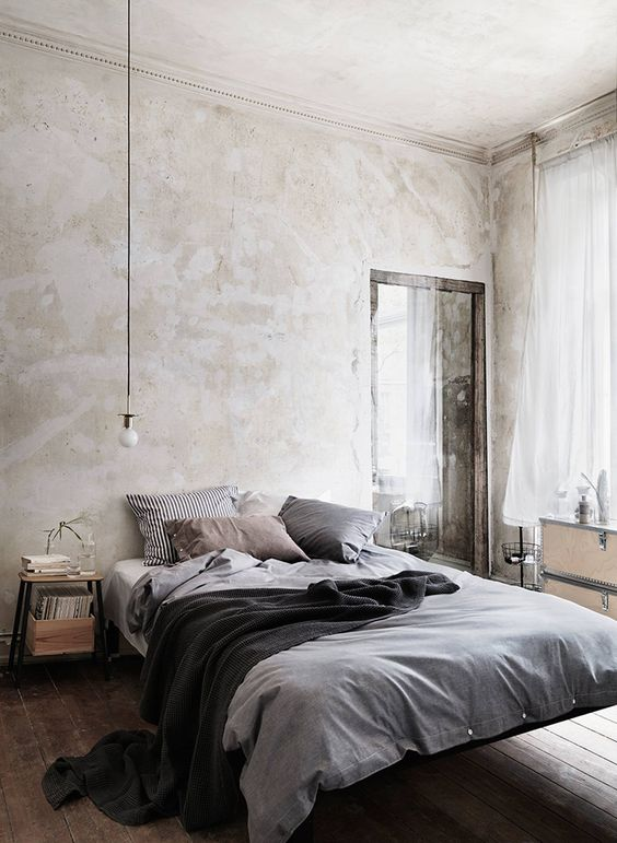 lighter concrete wall with natural stains light gray bed treatment black throw blanket rustic wood plank floors