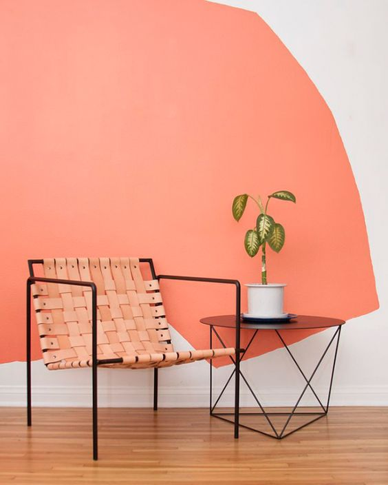 metal framed chair with light orange leather joints thin metal frame side table with round shaped top