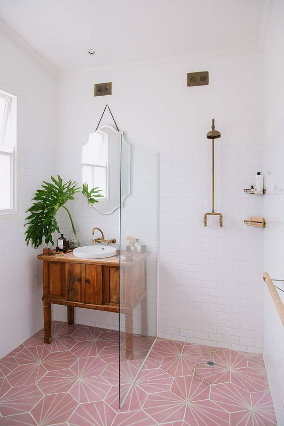 modern minimalist bathroom design walk in shower with clear glass partition modern tile floors in pink with white accent lines wood vanity counter with drawer and white sink greenery