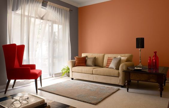 orange wall  gray wall crisp white sheer curtains area rug red armchair soft brown sofa with throw pillows