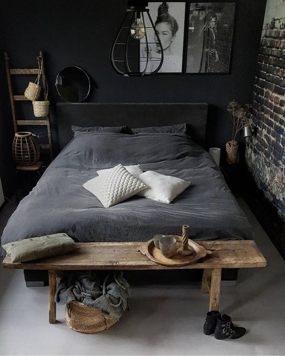 raw rustic bedroom design in black black painted brick walls black painted concrete walls gray concrete floors black velvet bedding treatment white throw pillows hardwood bench bed ornate wood ladder