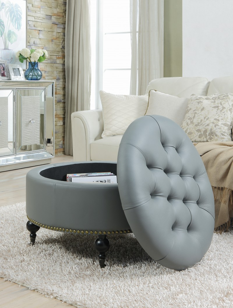 round tufted ottoman with gold nailhead trim at base