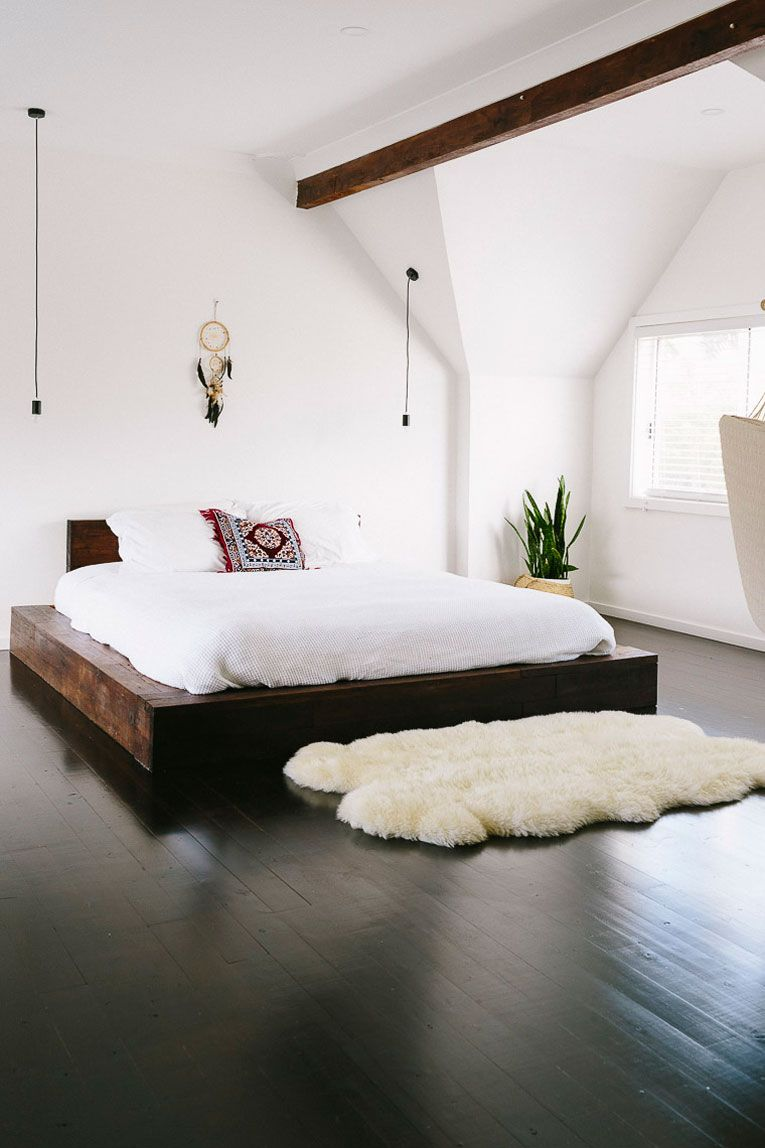 rustic minimalist bedroom design white walls dark wood floors platform wood bed frame white bedding treatment a Boho accent pillow white shag rug exposed wood beam
