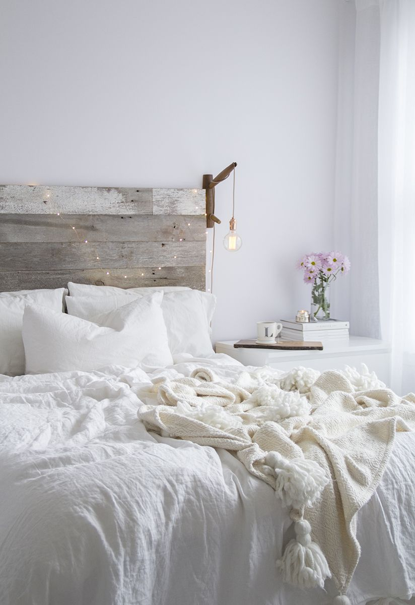 rustic minimalist bedroom with Nordic touch white bed treatment bed frame with wood headboard wall mounted night lamp white bedside table