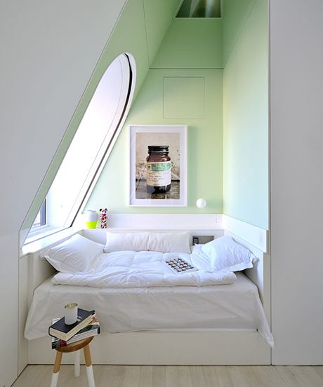 small attic reading nook with slanted ceiling with glass window fluffy cushion in white small side table