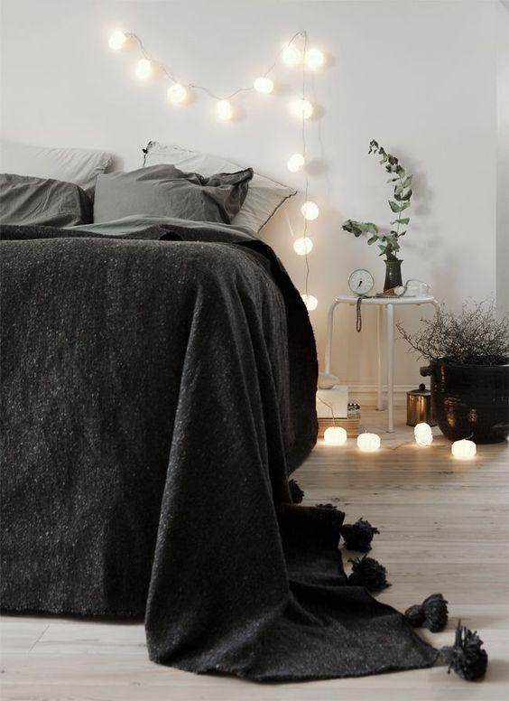 string bulb lighting idea white bedside table black duvet cover gray shams light wood floors crisp white walls