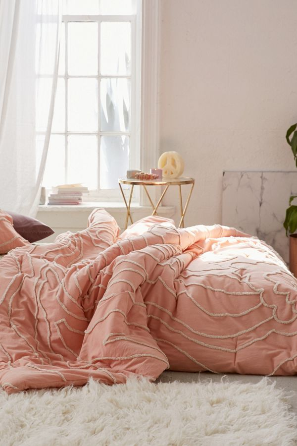 tufted floral patterned comforter in peach by Urban Outfitters