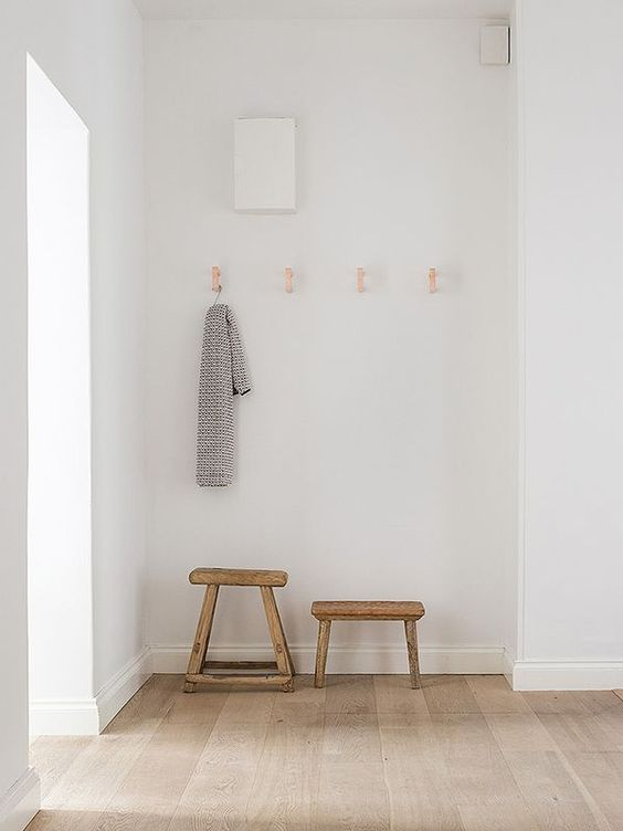 ultra minimalist hallway a couple of small wood bench some hooks mounted on wall