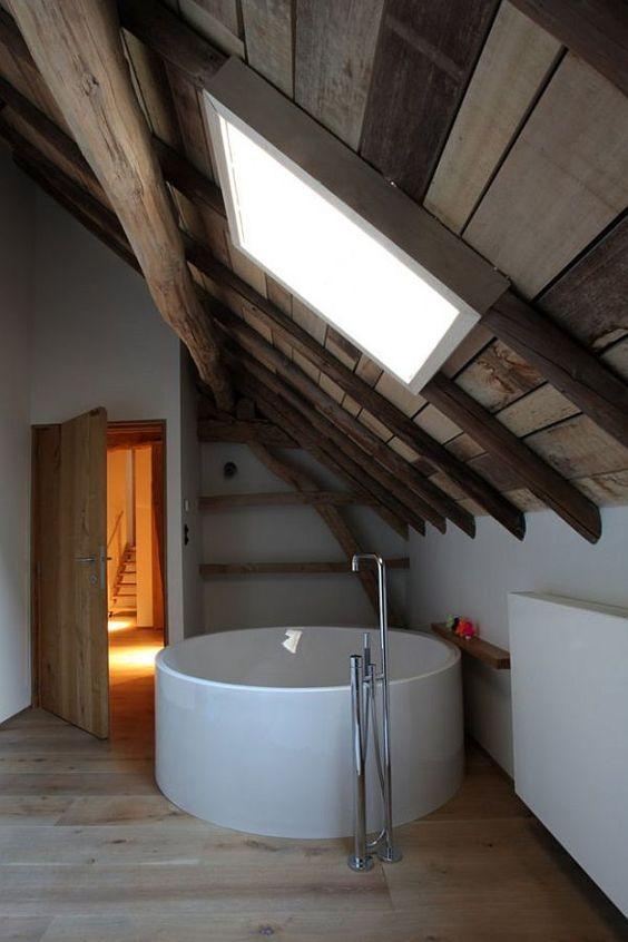 ultra modern bathroom wood plank ceilings with skylight modern white bathtub with standing steel faucet light wood floors exposed wood beams