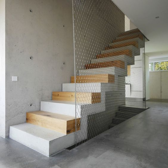 ultra modern interior staircase made of concrete oak plank supported with steel mesh railing system