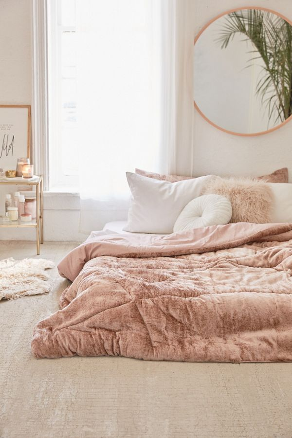 velvet comforter in mauve by Urban Outfitters round framed wall mirror brass side table white bed linen