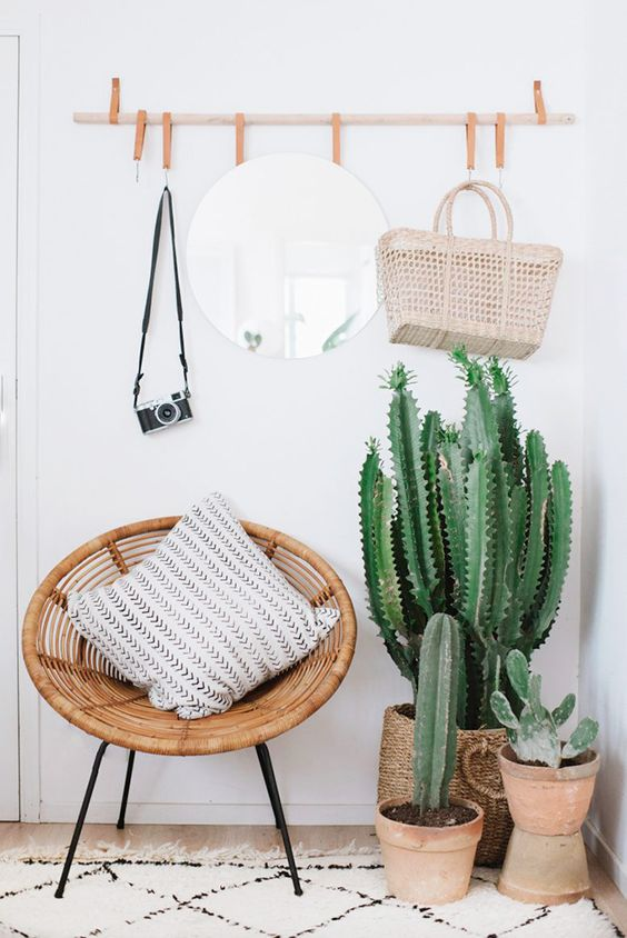 white vintage shag rug wicker egg chair with throw pillow burnt clay potted cacti frameless wall mirror in round shape