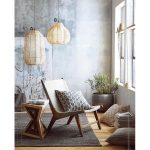Ariel Rattan Pendant With Creamy White Interior Lampshade Wooden Lounge Chair With Throw Pillow Wooden Side Table Gray Area Rug Wood Plank Floors
