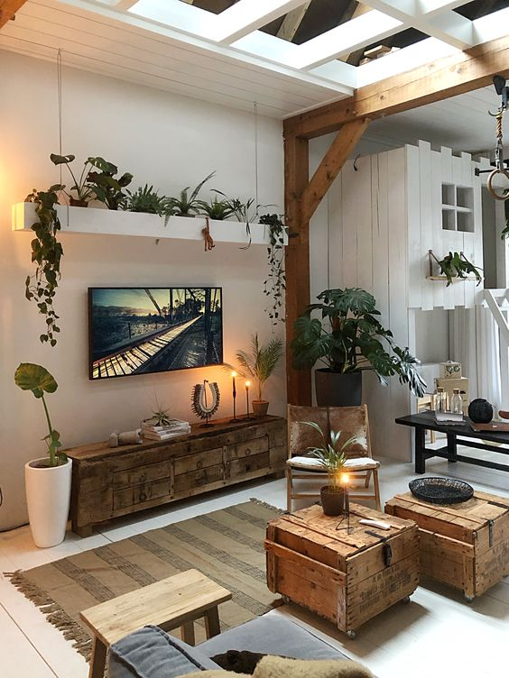 Bohemian area rug with tassels crate coffee tables rustic media table white vase some greenery exposed wood beams and pillars