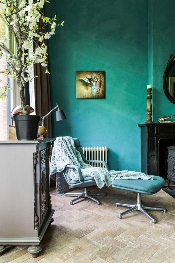 Marrs Green wall color accented with butterfly wall decor movable chair and table in blue herringbone tiled wood floors gray dresser with potted flowers on top