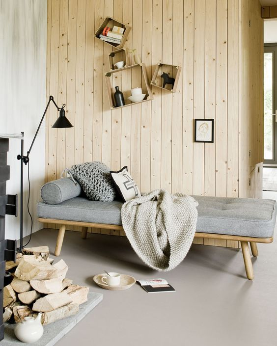 Scandi daybed with light wood frame gray cushion crochet throw wood plank walls modern industrial floor lamp