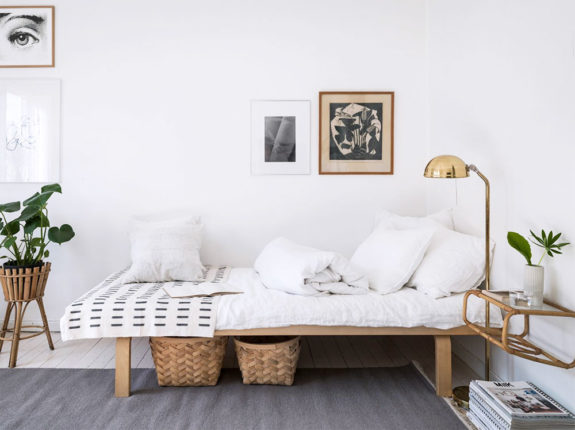 Scandinavian daybed with light wood frame and white cushion white throw pillows gray area rug decorative bamboo baskets bamboo pot for greenery