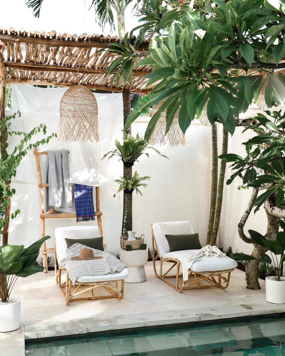 Villa Arjuna's pool area a couple of bentwood lounge chairs concrete side table in white wooden leaning ladder small log shade idea