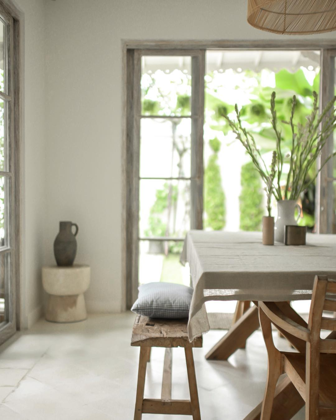 a set of teak dining furniture with gauze tablecloth and a throw pillow