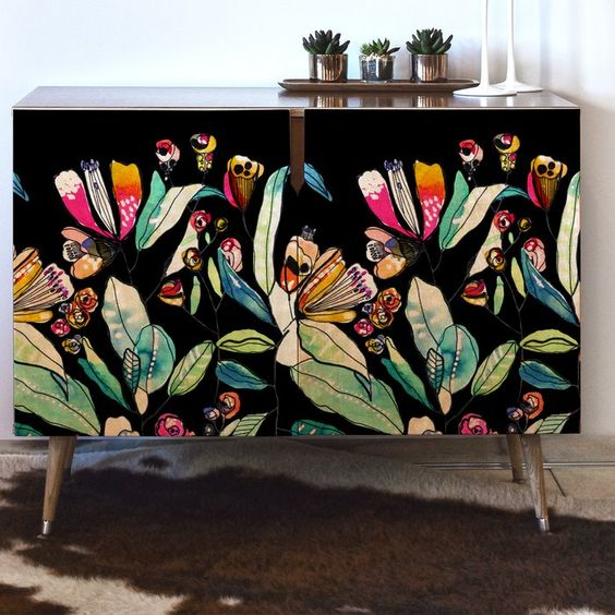 accent cabinet with black backdrop and vividly colored floral patterns