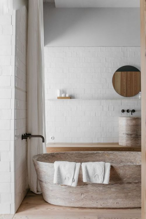 airy and bright bathroom white subway tile walls floor to ceiling white curtains soft toned stone bathtub light wood floors