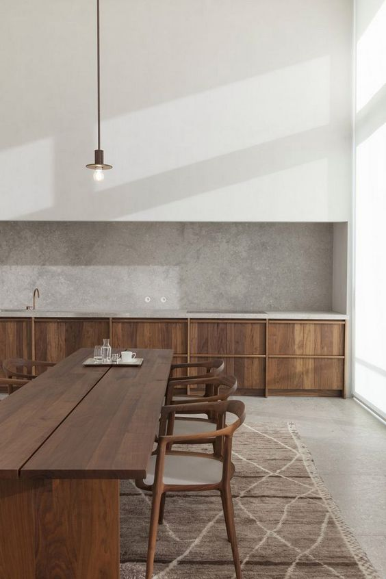 area rug with modern white line accents dark wood dining furniture wood kitchen cabinets concrete finish backsplash white walls long cabled pendant