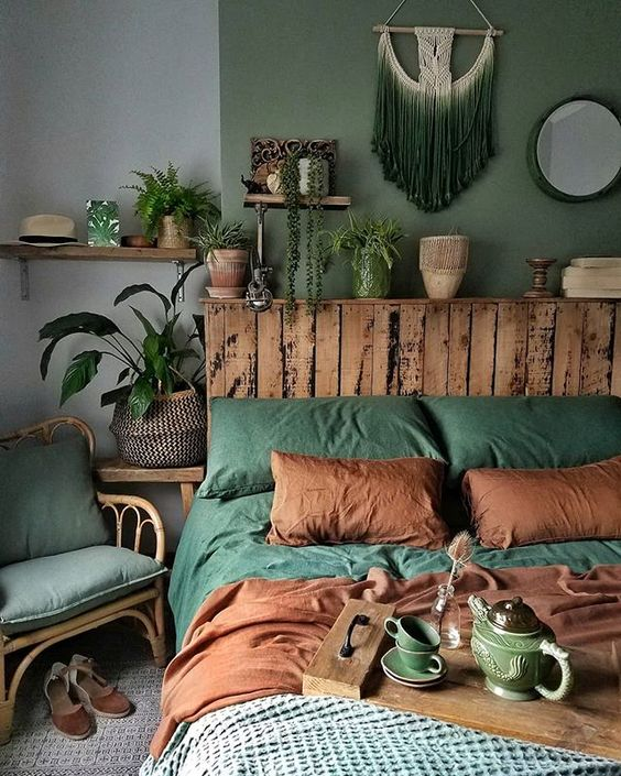 bed frame with rustic headboard green macrame hanging wall decor green bed linen and pillows earthy brown pillows and blanket rattan chair with cushion some house plants