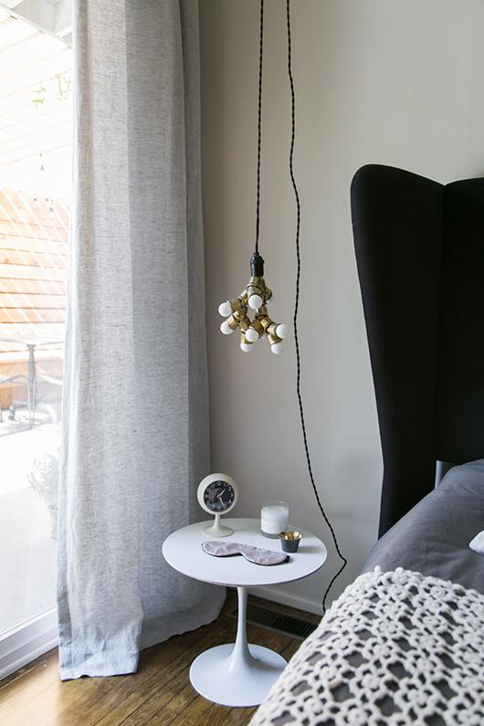 bright and airy bedroom for good atmosphere unique hanging lamp white round top side table in Scandinavian style wood floors light gray draperies