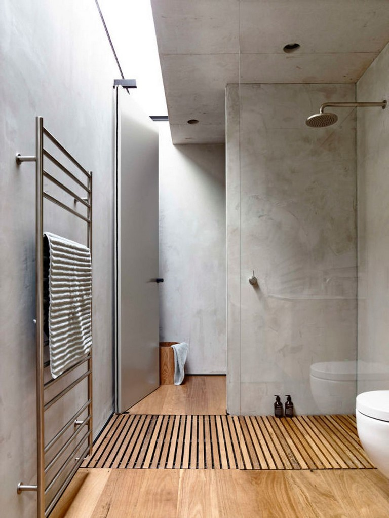 clean line and minimalist bathroom concrete walls and ceilings wood floors stainless steel bathroom utensil walk in shower with clear glass panel