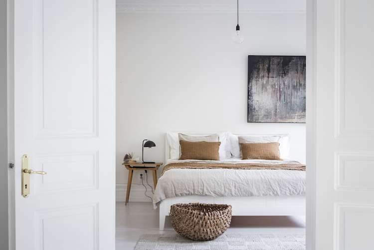 clean look and airy bedroom broken white bed linen with rust shams and blanket wicker basket midcentury modern wood bedside table