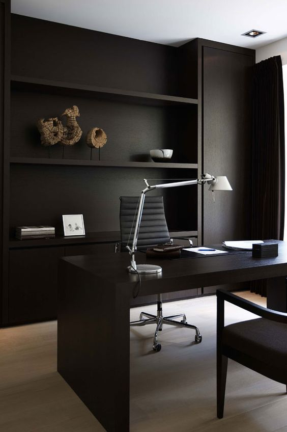contemporary home office with dark textural and rustic richness black working desk movable working chair black shelves