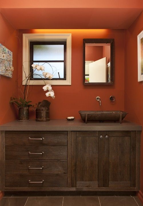 dark wood bathroom vanity with dark wood countertop and sink rust colored walls