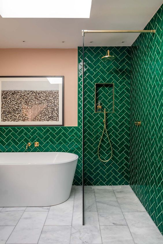 emerald tiled walls white tiled floors modern white bathtub walk in shower with clear glass panel and brass hardware