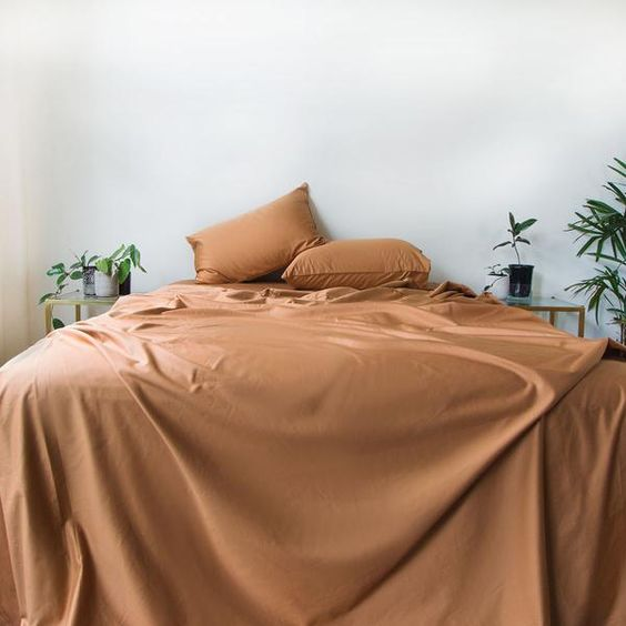 flat sheet bed cover in terracotta terracotta pillows white walls