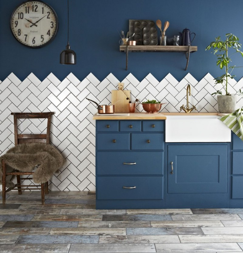 herringbone shaped metro tiled walls in white bold blue conventional walls bold blue kitchen cabinets and wood countertop dark wood chair rustic wood plank floors