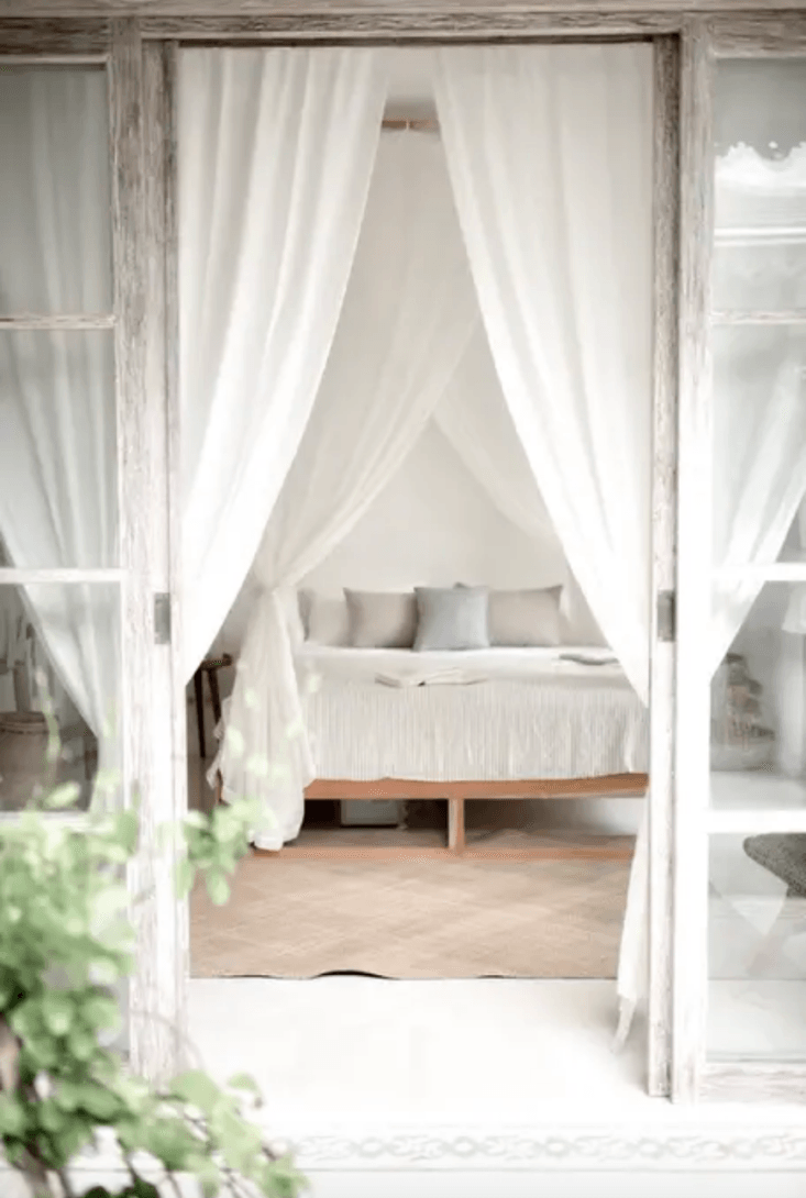 huge glass doors with white draperies woven area rug teak furniture teak window and door frames