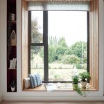 Low Profile Bay Window With Inner Wooden Plank Finish Outer White Concrete Frame And Narrow Book Shelf