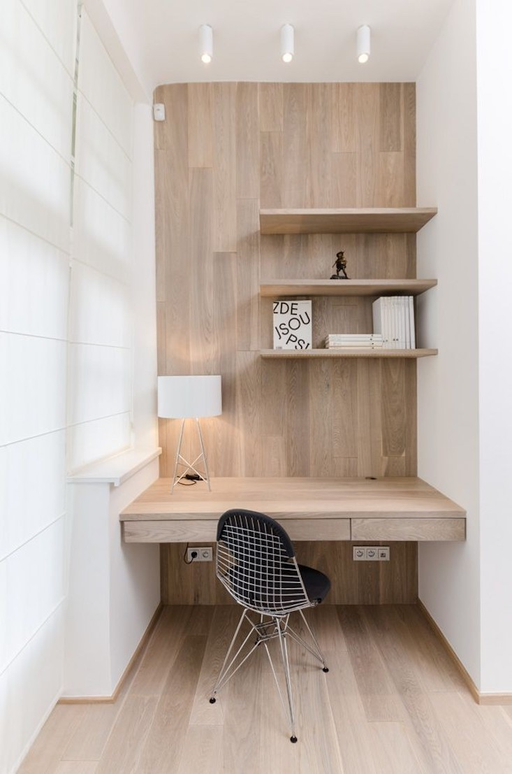 minimal home office in Scandinavian style light wood wall paneling built in wood shelves light wood working desk with additional drawers black chair with wire structure