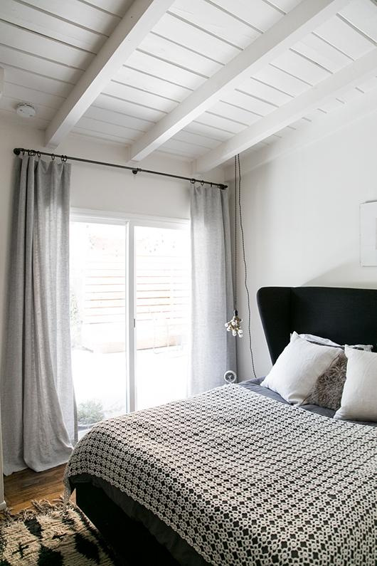 modern bohemian bedroom design monochromatic bed linen white shams ultra light draperies white wood plank ceilings with exposed beams in white black bed frame with black headboard wood floors