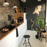 Modern Industrial Kitchen Brick Walls Wood Countertop With White Flat Cabinets Wood Bench For Plants A Metal Stool With Round Top